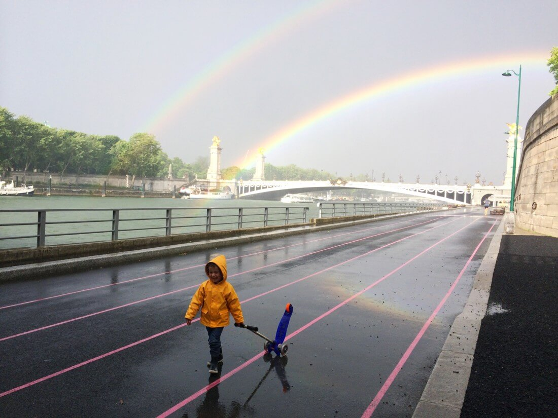 boy in front of a double rainbow