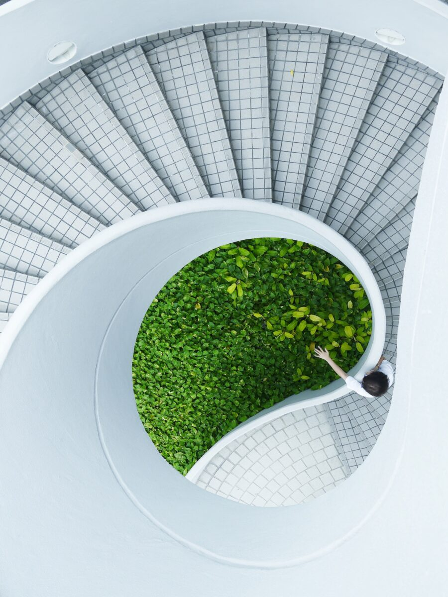 A view of a spiral staircase with a woman reaching out to touch greenery in the middle.